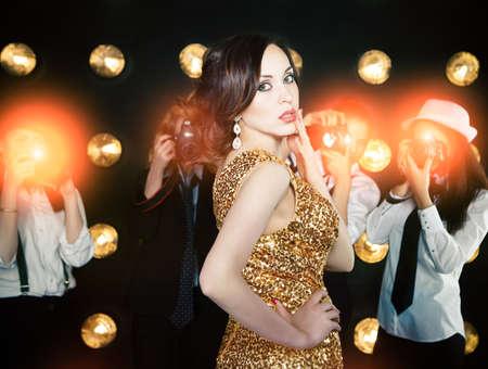Superstar vrouw met gouden glanzende jurk poseren voor paparazzi