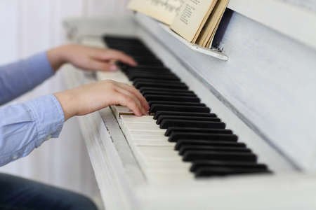Close up of hands of the boy playing piano. Concept of music and entertainment photo