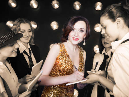 superstar: Superstar woman wearing golden shining dress crowded by paparazzi Stock Photo
