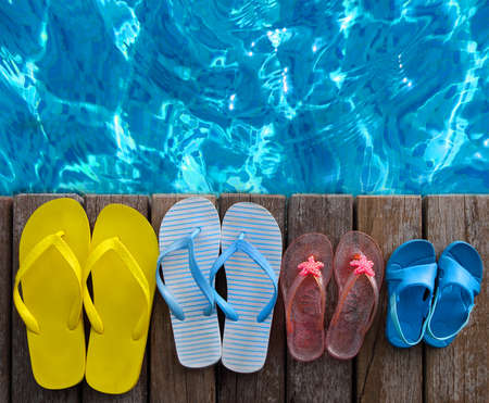 Brightly colored flip-flops of the family on wooden background near the pool. Summer travel and vacation concept