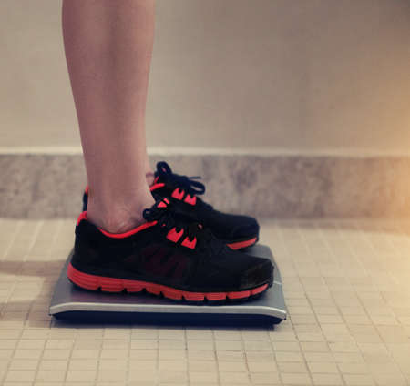 weight control: Female bare feet with weight scale in the sport gym Stock Photo