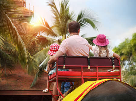 Man and his daughters riding on the back of elephant in Thailand