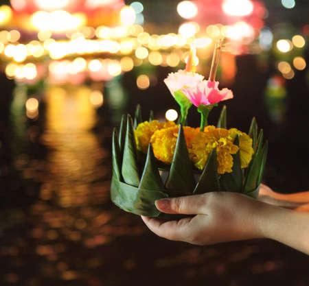 Frau hält Boot mit Kerzen und Blumen für Thailands traditionelle Loy Krathong Festival gegeben. DOF. Foto in der Bewegung und in der Dunkelheit Standard-Bild