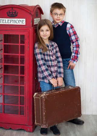 suit case: Portrait of a happy girl and a smiling boy with suit case. Travel concapt