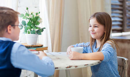little table: Happy little boy and girl drinking tea and talking in cafe