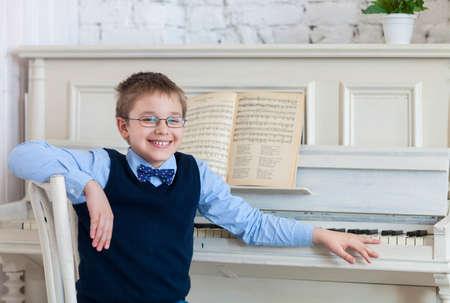 tocando piano: Niño pequeño que juega el piano en casa. Concepto de la música Foto de archivo