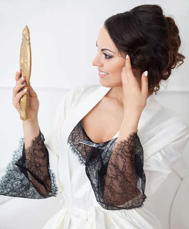 fresh graduate: Gentle young bride looks in the mirror. Bridal morning Stock Photo