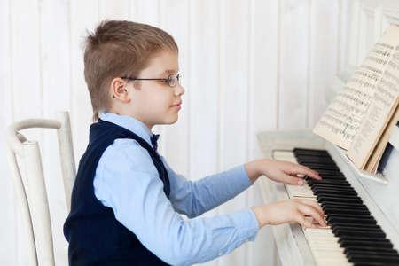 fortepian: Mały chłopiec gra na fortepianie w domu. Koncepcja muzyki