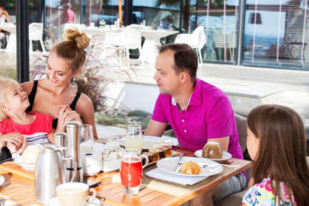 brunch: Happy family having brunch outside on a sunny day Stock Photo