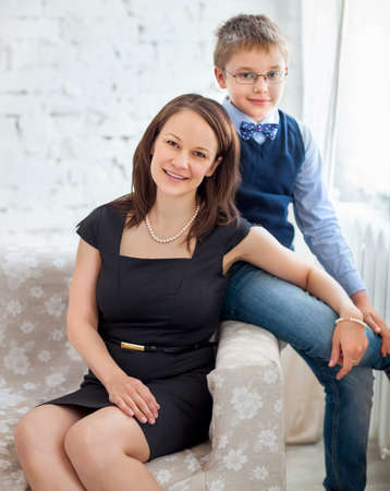 madre soltera: Madre e hijo se abrazan en la sala de estar Foto de archivo