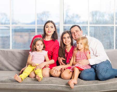 felicidade: Família nova feliz com as crianças perto da janela em casa Imagens
