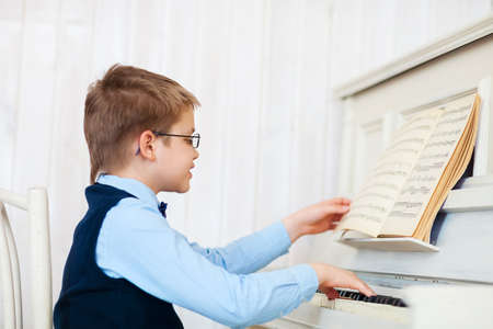Little boy playing piano at home. Concept of music photo