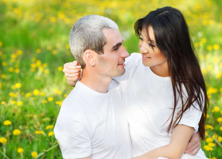 Young loving couple at the green grass with dandelion in the park park photo