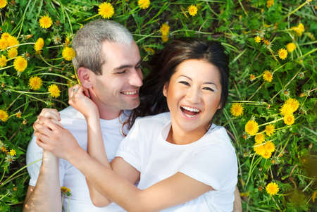 Young loving couple lying at the green grass with dandelion in the park park photo