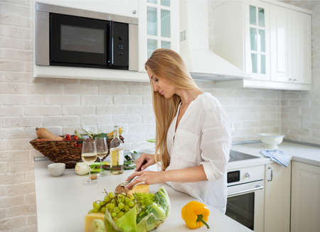 Young smiling woman cooking vegetables at the kitchen photo