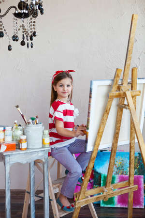 looking over: Little artist girl holding a paintbrush and looking over a canvas on an easel. Concept of creativity and fun Stock Photo