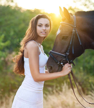 caresses: Portrait beautiful happy woman with long hair next horse Stock Photo