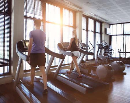 personas trotando: Hombre sano y la mujer corriendo en una cinta en un gimnasio. Deporte y salud concepto