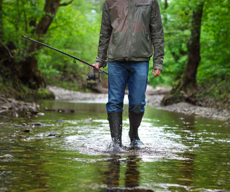 uomo sotto la pioggia: Fisherman with fly-fishing on mountain river wearing rain boots. Spring time