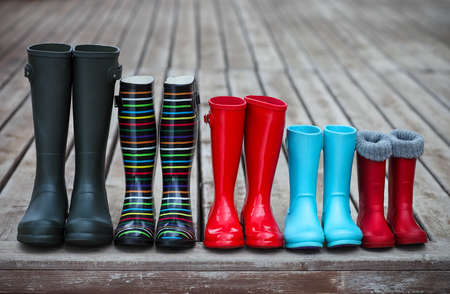 medium shot: Five pairs of a colorful rain boots. Family concept Stock Photo