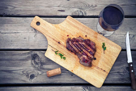 BBQ steak. Barbecue grilled beef steak meat with red wine and knife. Healthy food. Barbeque steak dinner