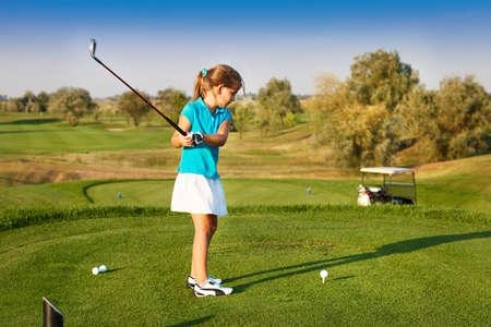 Het leuke meisje spelen golf op een veld buiten. Zomertijd Stockfoto