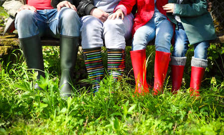 Happy family wearing colorful rain boots. Family concept