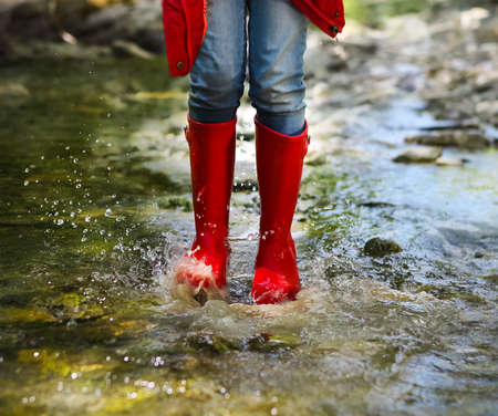 Child wearing red rain boots jumping into a mountain river. Close up