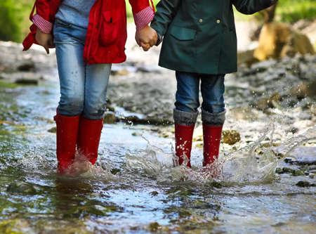 山の川に飛び込む長靴を身に着けている子供。クローズ アップ