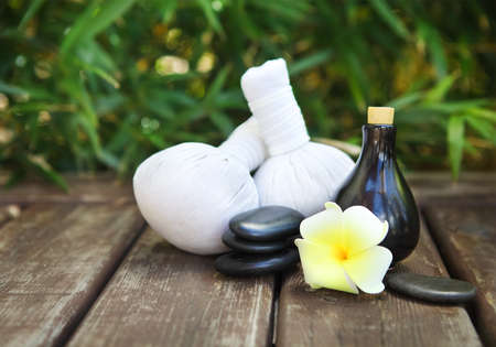 bathsalt: Spa theme objects with frangipani flower, compress balls, stacked basalt stones and bamboo background Stock Photo