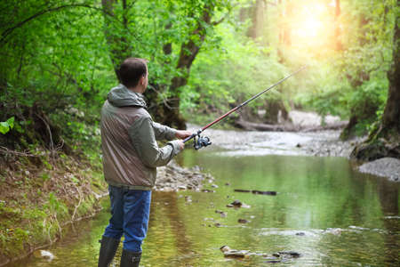 flyfishing: Fisherman with fly-fishing on mountain river. Spring time