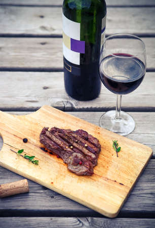 food and wine: BBQ steak. Barbecue grilled beef steak meat with red wine. Healthy food. Barbeque steak dinner Stock Photo