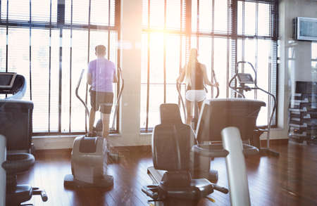 Healthy couple training on a treadmill in a sport centre