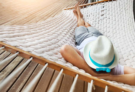 Lazy time. Man in hat in a hammock on a summer day 스톡 콘텐츠