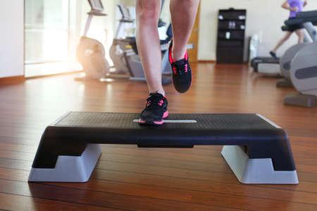 gimnasia aerobica: Aeróbic paso. Recorta la imagen de mujer hermosa que hace aeróbicos jóvenes paso mientras en club de salud
