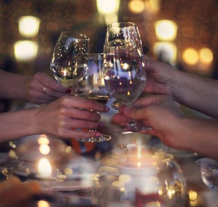 wine: Celebración. Las personas titulares de los vasos de vino blanco haciendo un brindis. Noche acogedora en un restaurante