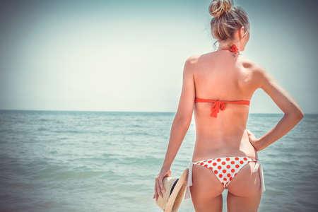 ビーチでセクシーなビキニの美しい若い女性。夏の休日の概念