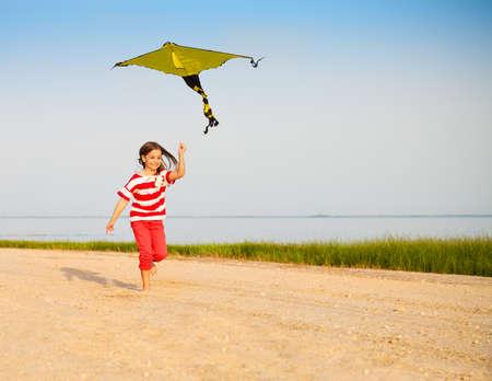 Weinig gelukkig lopende meisje met vliegende vlieger op het strand bij zonsondergang