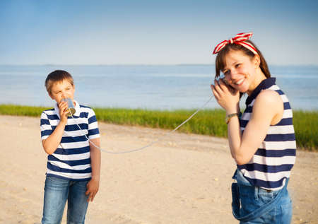 Kids having a phone call with tin cans on sea background Stockfoto