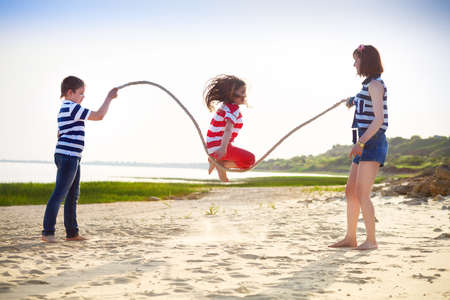 tug: Summer family vacation - girl playing with skipping rope on the beach Stock Photo