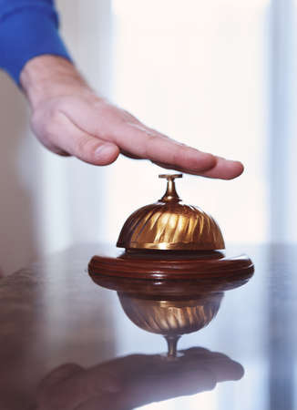 businessman waiting call: Hand of a man using a hotel bell in retro style