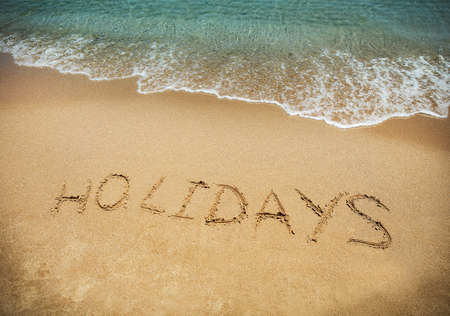 beach holiday: Happy Holidays! Written in sand at the beach. Holiday concept. Stock Photo
