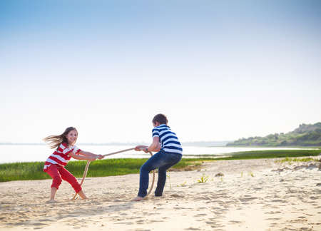 forces: Tug of war - boy and girl playing on the beach. Summer holiday and family power concept