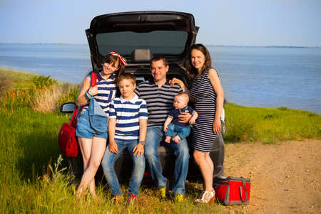 Family of five having fun on the beach going on summer vacation. Car travel and summer vacation concept Foto de archivo