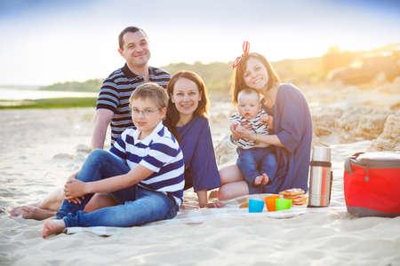 family picnic: Familia de cinco en el picnic en la playa. Concepto de las vacaciones de verano