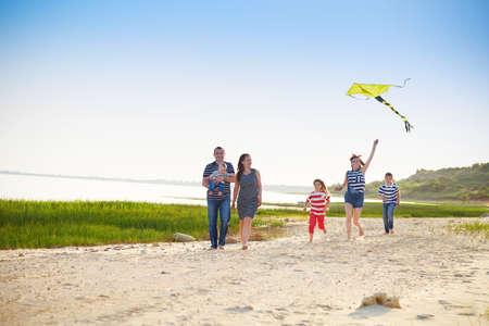 papalote: Familia joven feliz con volar una cometa en la playa. Vacaciones de verano Foto de archivo