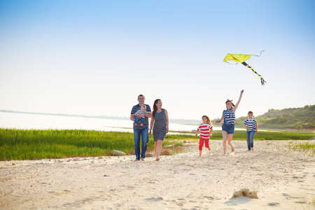 blue romance: Happy young family with flying a kite on the beach. Summer vacation