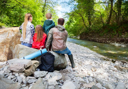 botas de lluvia: Familia joven feliz con dos hijas pequeñas cerca del río de montaña al aire libre