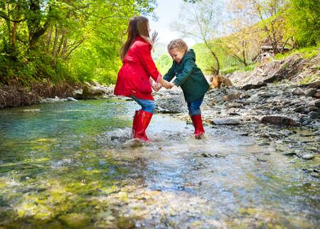 Felices los niños vistiendo botas de lluvia que saltan en un río de montaña