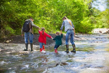 botas de lluvia: Familia joven feliz con dos hijas pequeñas en caminata de montaña Foto de archivo